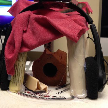 Photograph of Eric's object from Jody Shipka's Evocative Objects workshop--a small temple made of a frisbee, rolled-up newspaper, a brick, and a small blanket